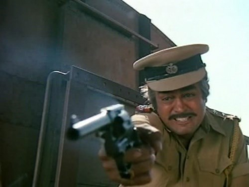 Thakur fires his revolver. A short ejector rod under the barrel matches a Colt model.